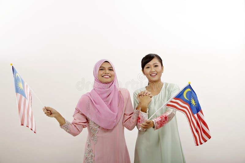 Merdeka. Two malay women holding malaysia flag stock images