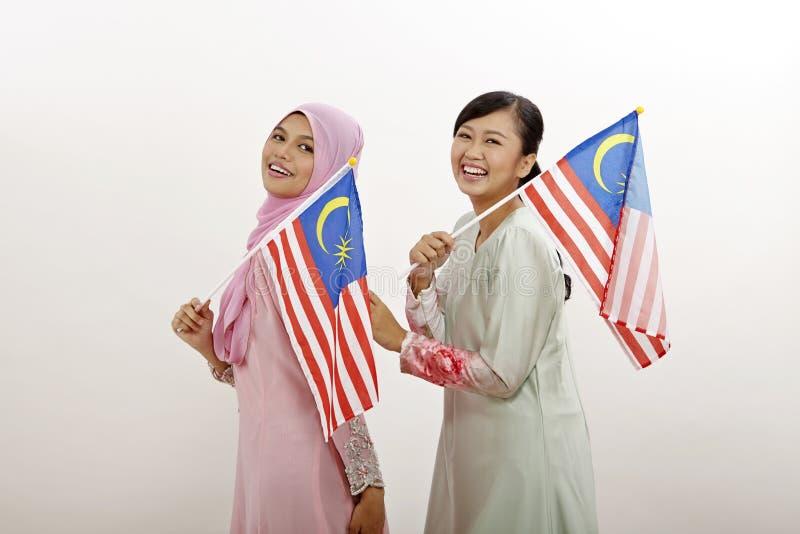 Merdeka. Two malay women holding malaysia flag royalty free stock photos