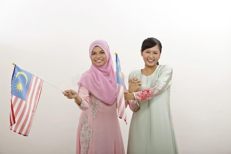 Merdeka. Two malay women holding malaysia flag royalty free stock image