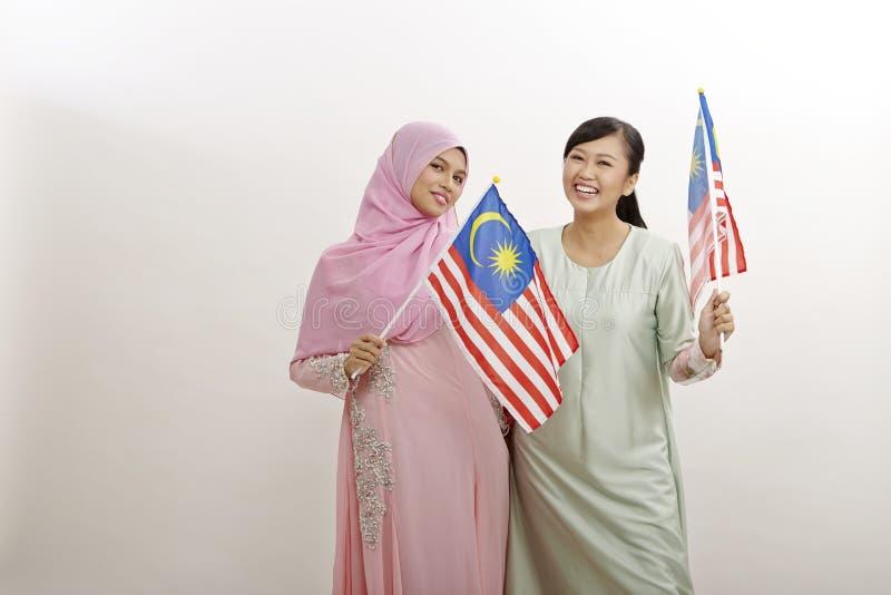 Merdeka. Two malay women holding malaysia flag stock image