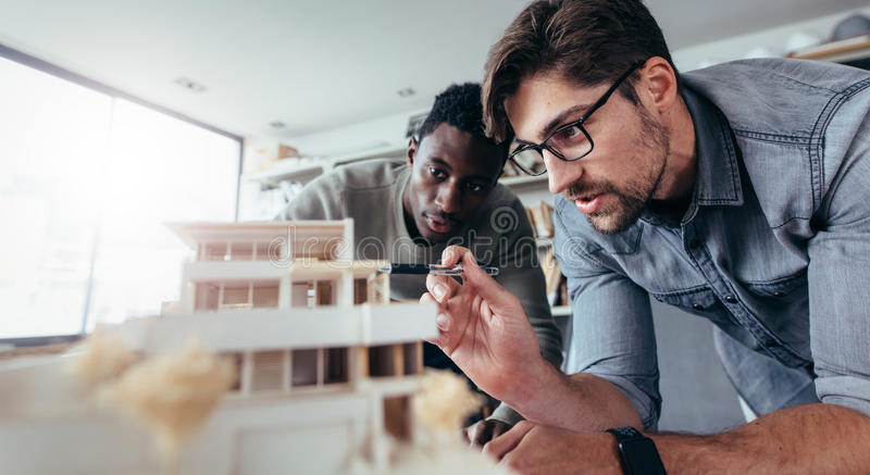 Two male architects discussing over house model stock photography