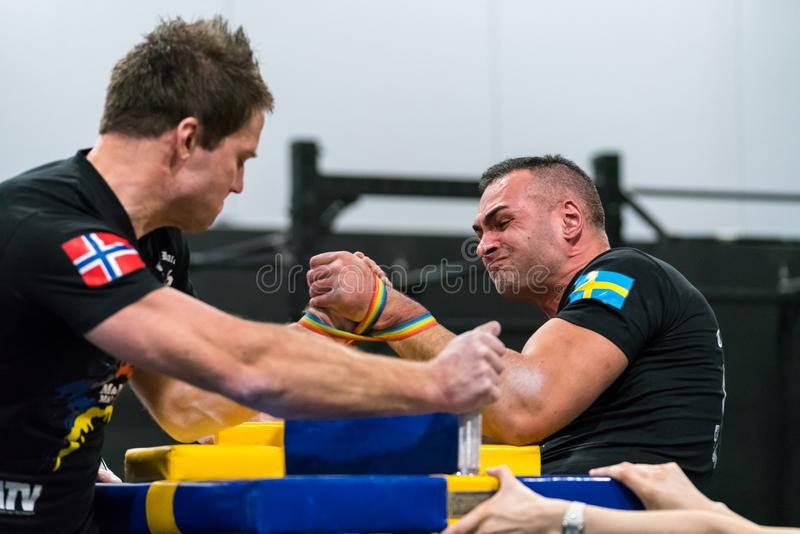 Two male arm wrestlers and referees in a tough fight. STOCKHOLM, SWEDEN - JANUARY 13, 2018: Profile view of a Swedish and Norwegian male arm wrestler in a match royalty free stock photos