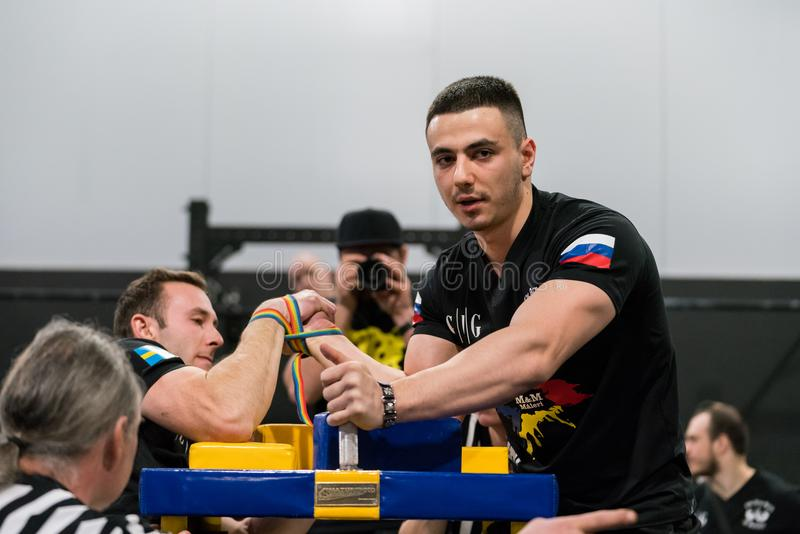 Two male arm wrestlers and referees in a tough fight. STOCKHOLM, SWEDEN - JANUARY 13, 2018: Profile view of a Swedish and Russian male arm wrestler and a stock images