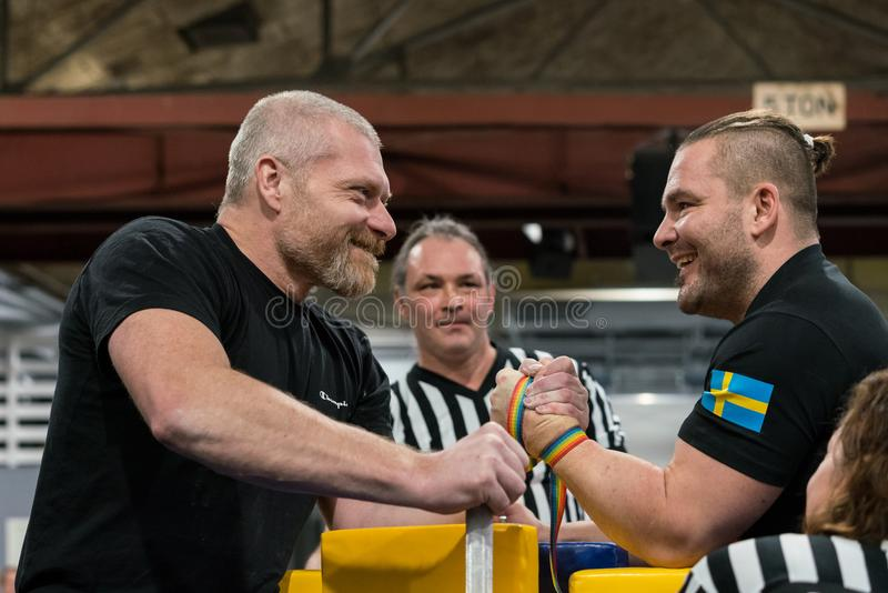 Two male arm wrestlers and referees in a tough fight. STOCKHOLM, SWEDEN - JANUARY 13, 2018: Profile view of two Swedish male arm wrestlers and a referee in a royalty free stock photo