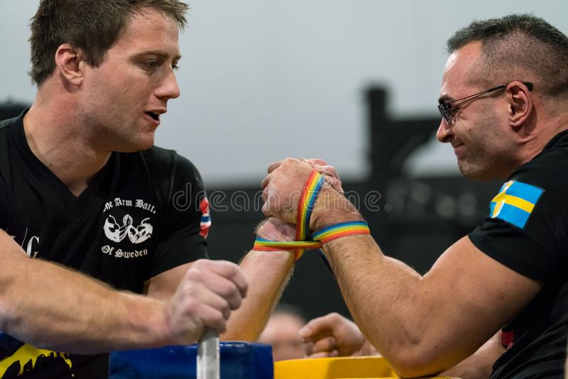 Two male arm wrestlers in a tough fight. STOCKHOLM, SWEDEN - JANUARY 13, 2018: Profile view of a Swedish and Norwegian male arm wrestler in a match at the event royalty free stock image