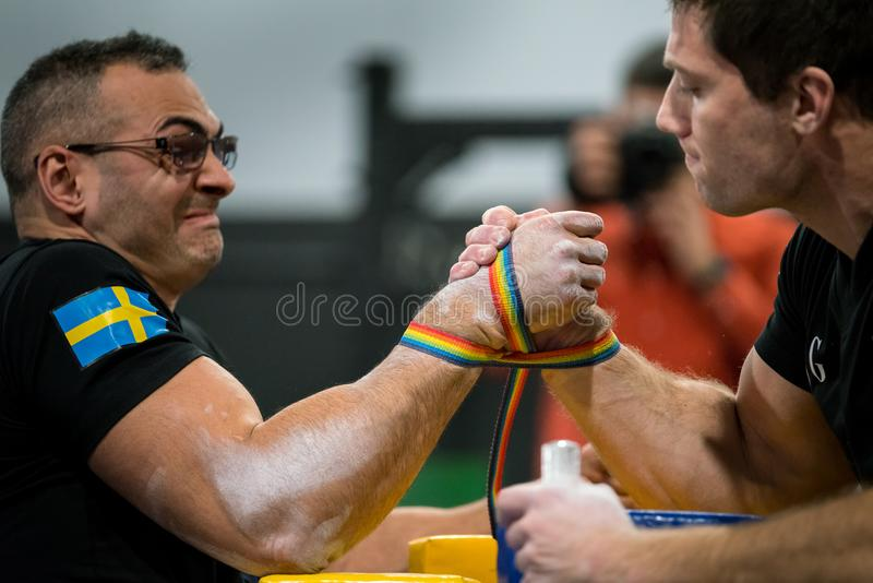 Two male arm wrestlers in a tough fight. STOCKHOLM, SWEDEN - JANUARY 13, 2018: Profile view of a Swedish and Norwegian male arm wrestler in a match at the event stock image