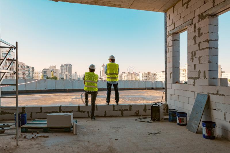 Two male builders at a construction site. Men looking into the distance to the panorama of the city. Building, development, teamwo stock photography