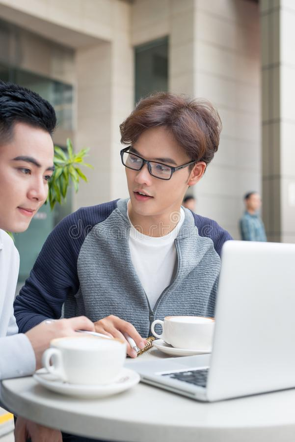 Two male businessmen sitting in cafe and discussing business pro royalty free stock photos