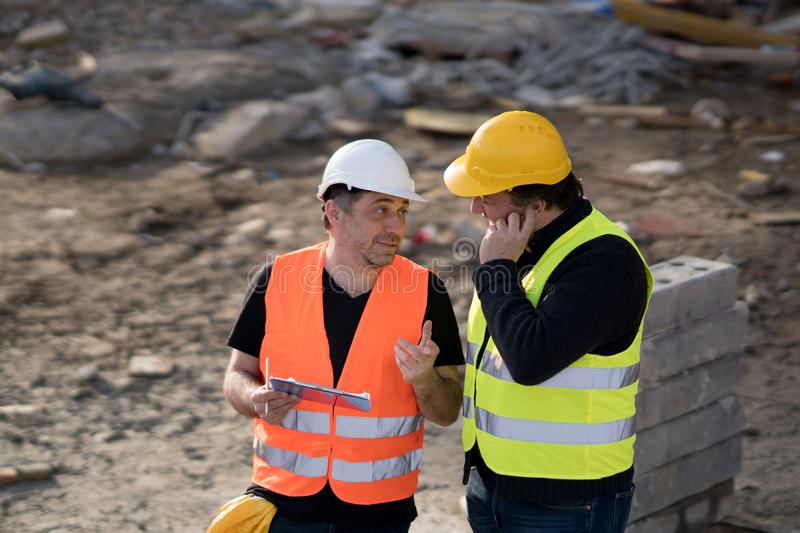 Civil engineers at work on construction site. Two male civil engineers wearing protective vests and helmets at work on construction site royalty free stock photos