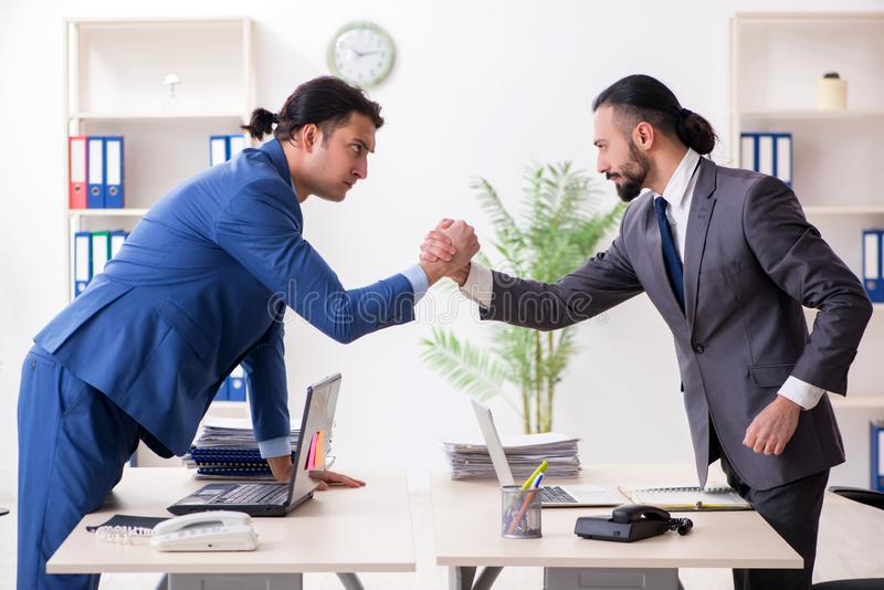 The two male colleagues in the office. Two male colleagues in the office stock photo