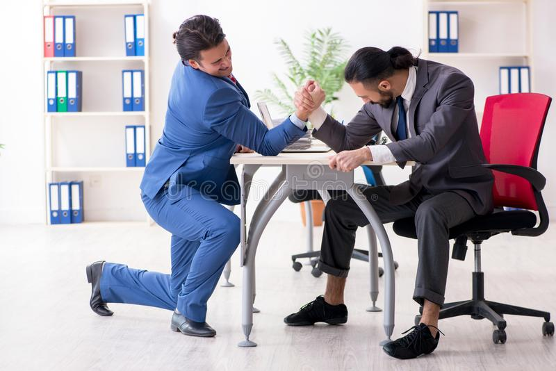 Two male colleagues in the office. The two male colleagues in the office stock image