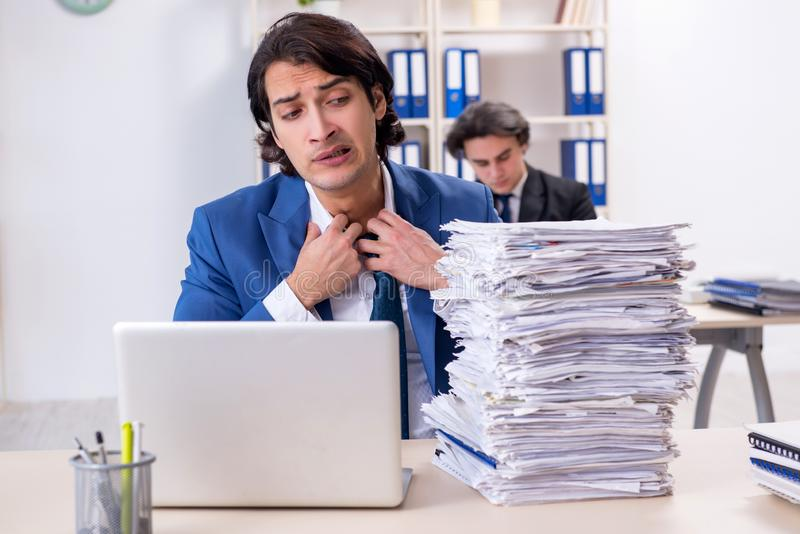 Two male colleagues unhappy with excessive work. The two male colleagues unhappy with excessive work royalty free stock images