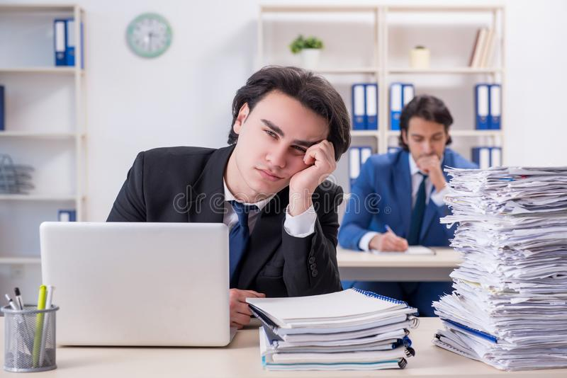 Two male colleagues unhappy with excessive work. The two male colleagues unhappy with excessive work royalty free stock photos