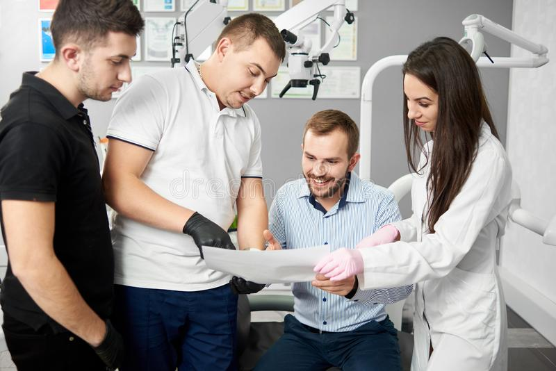 Two male dentists and their female assistant are showing the paper to a satisfied male client of the dental office royalty free stock photo