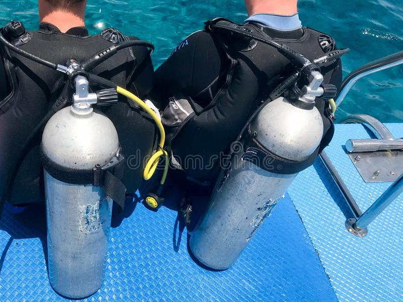 Two male divers in black diving waterproof suits with shiny metal aluminum canisters are preparing to dive from the boat to the bl royalty free stock photography