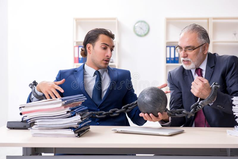 Two male employees unhappy with excessive work. The two male employees unhappy with excessive work royalty free stock images