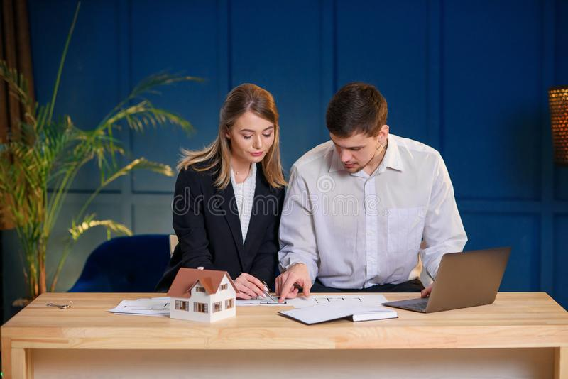 Two male and female architects discussing design of new house, flat. royalty free stock photos
