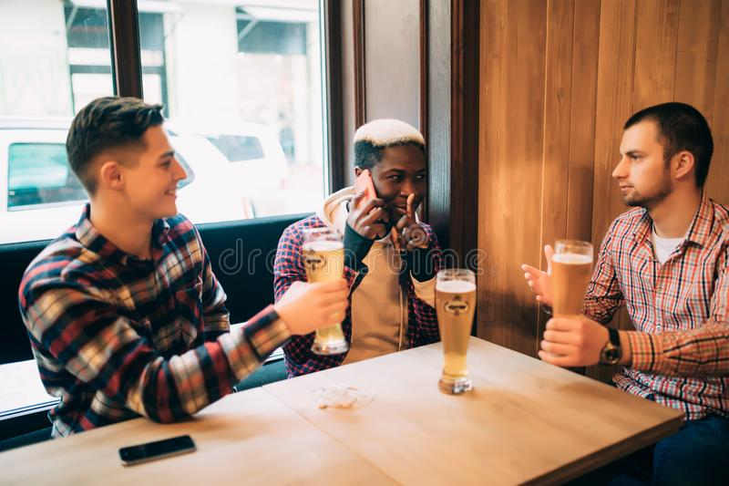 Two male friends in bar are drinking beer and communicating while one is talking on phone and asking for silence. Friends meet in stock photo
