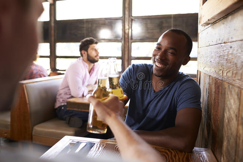 Two male friends in a bar making a toast with beer bottles stock photo