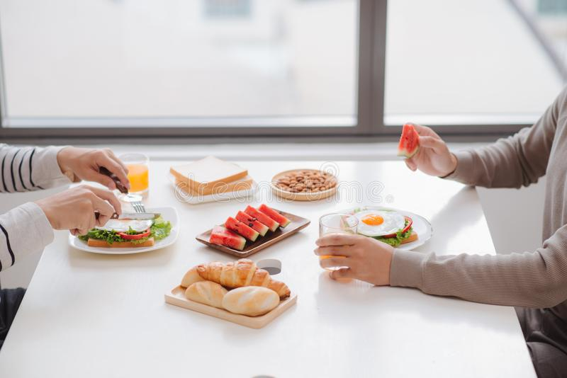 Two male friends eating breakfast at home in morning. royalty free stock image