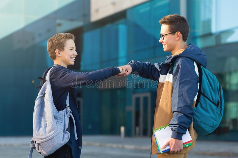 Two male friends meeting oudoors, teenagers greeting each other royalty free stock photos