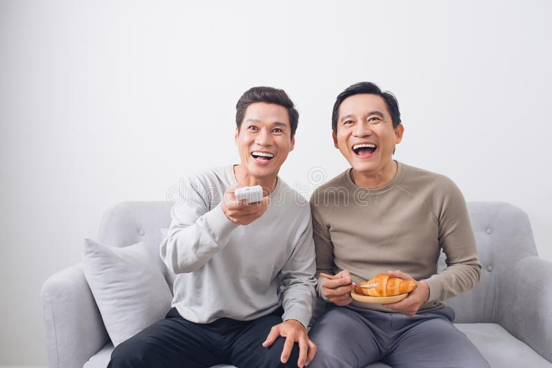 Two male friends watching football sitting on sofa at home royalty free stock image