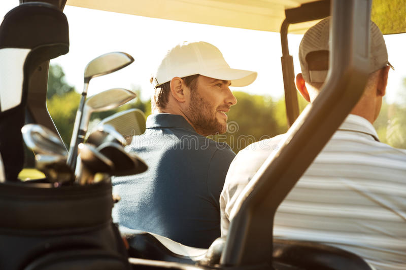Two male golfers sitting in a cart stock image
