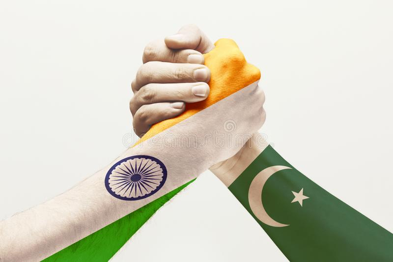 Two male hands competing in arm wrestling colored in Pakistan and India flags stock image