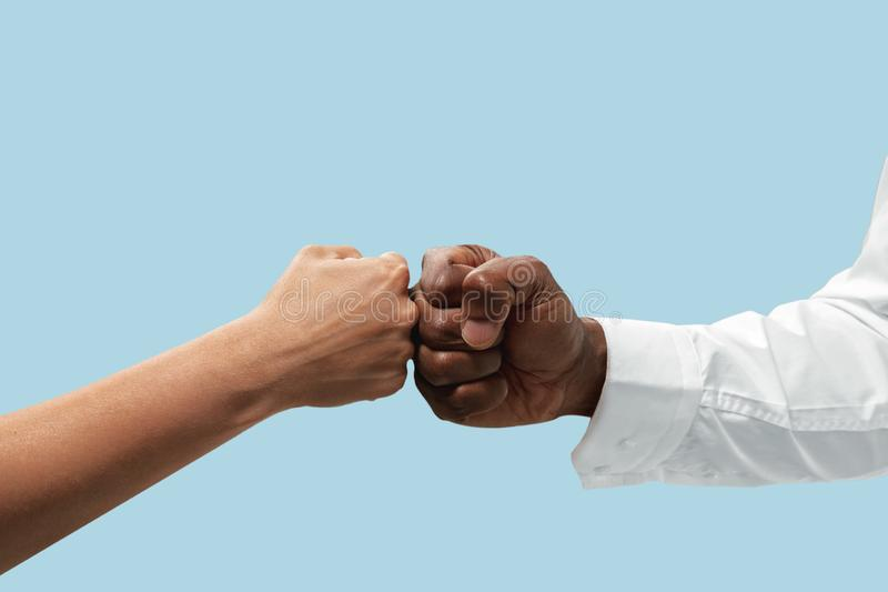 Two male hands competion in arm wrestling isolated on blue studio background. Friends greetings sign or disagreement. Two male hands competion in arm wrestling royalty free stock image