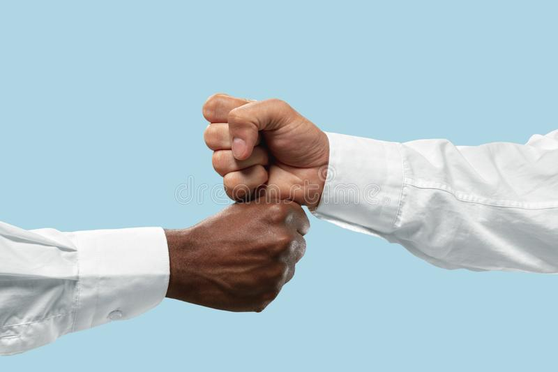 Two male hands competion in arm wrestling isolated on blue studio background. Friends greetings sign or disagreement. Two male hands competion in arm wrestling royalty free stock photography