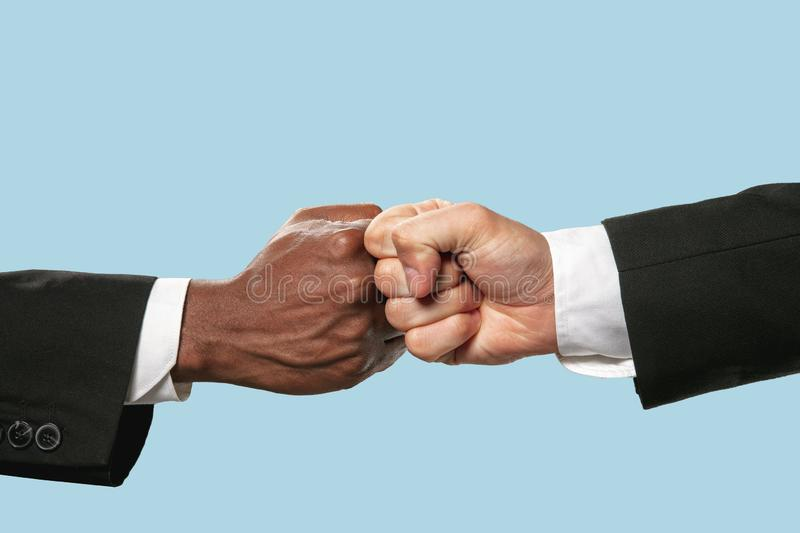 Two male hands competion in arm wrestling isolated on blue studio background. Friends greetings sign or disagreement. Two male hands competion in arm wrestling royalty free stock photos