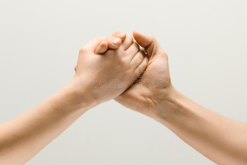 Two male hands competion in arm wrestling isolated on grey studio background. Don`t fight, let`s be friends. Two male hands competion in arm wrestling isolated stock image