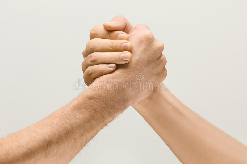 Two male hands competion in arm wrestling isolated on grey studio background. Friends greetings sign or disagreement. Two male hands competion in arm wrestling royalty free stock image