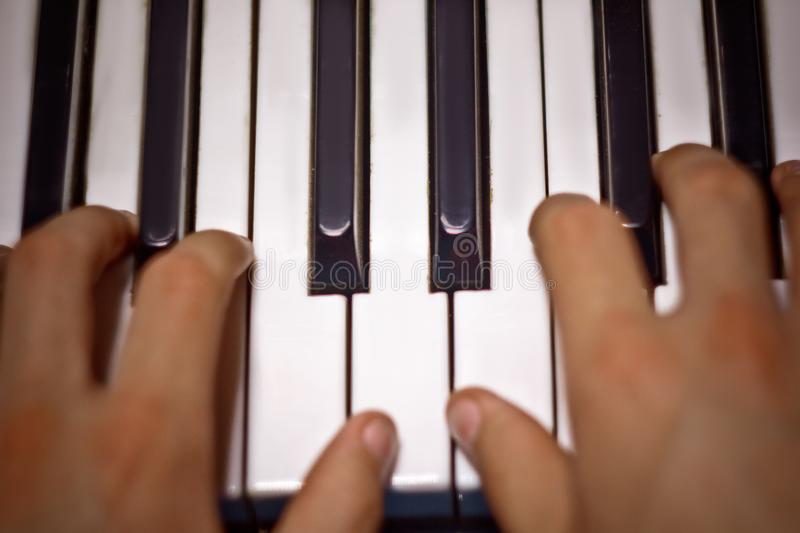 Two male hands on the piano. palms lie on the keys and play the keyboard instrument in the music school. student learns to play. stock photography