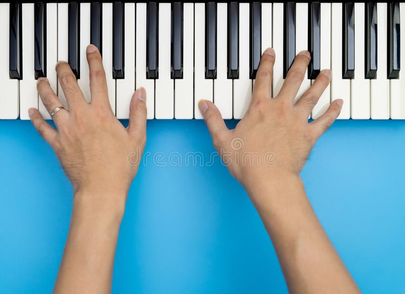 Two male hands playing on music keyboard on blue royalty free stock photography