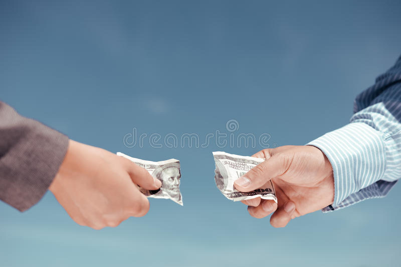 Two male hands tearing apart dollar banknote in. Concept photo of two hands pulling apart money banknote on light blue background stock photography