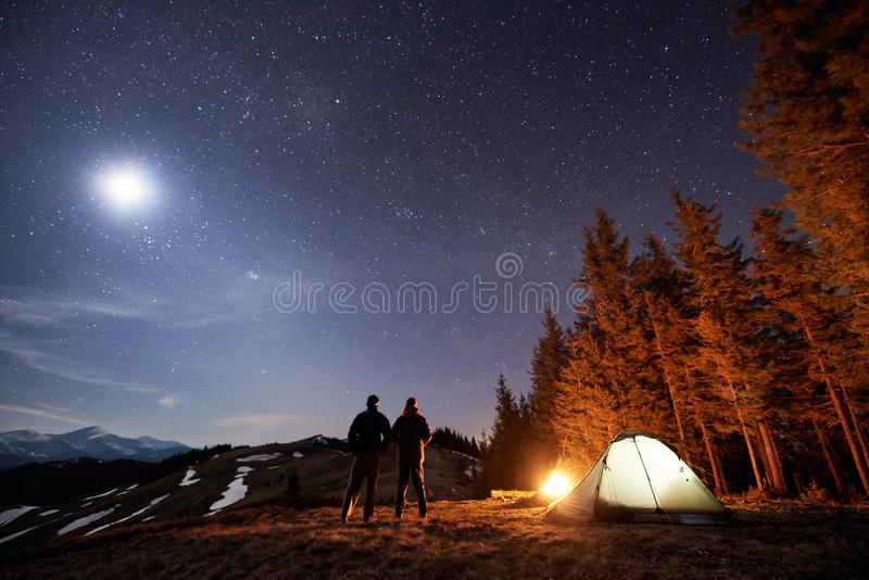 Two male hikers have a rest in his camp near the forest at night under beautiful night sky full of stars and the moon stock photo