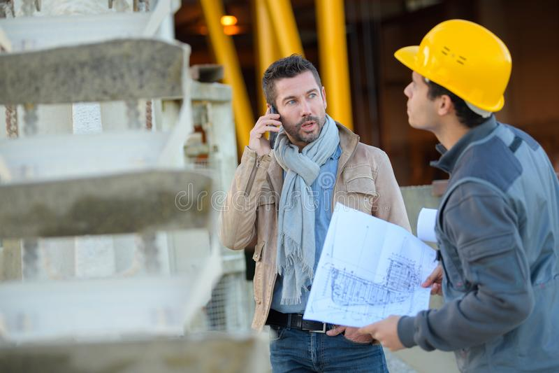 Two male industrial engineers looking at techincal drawing plans stock photos