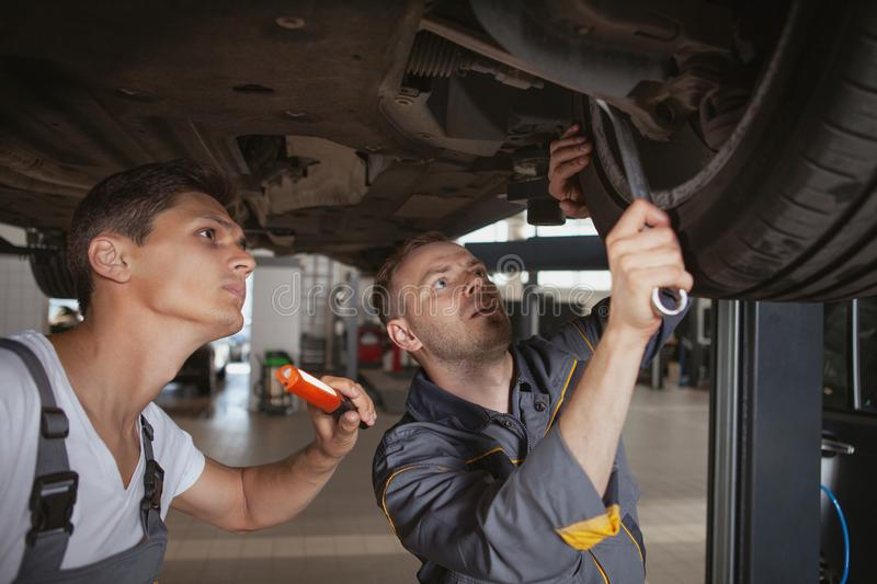 Two male mechanics working at the garage. Two car mechanics working underneath a broken vehicle at the garage. Experienced auto technicians making adjustments on stock images