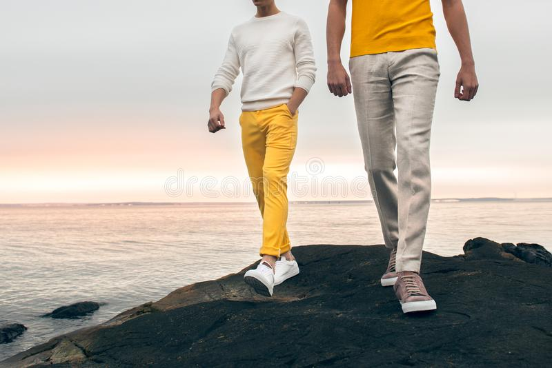 Two male models wearing fashionable spring summer outfit with colorful pants, t-shirt, sweater and shoes walking outdoors royalty free stock photo