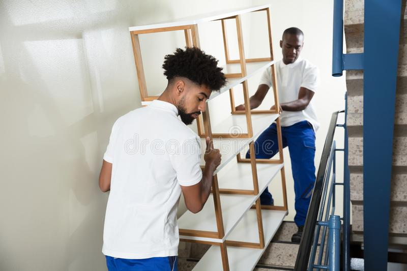 Two Male Movers Carrying The Empty Shelf At Home royalty free stock photography