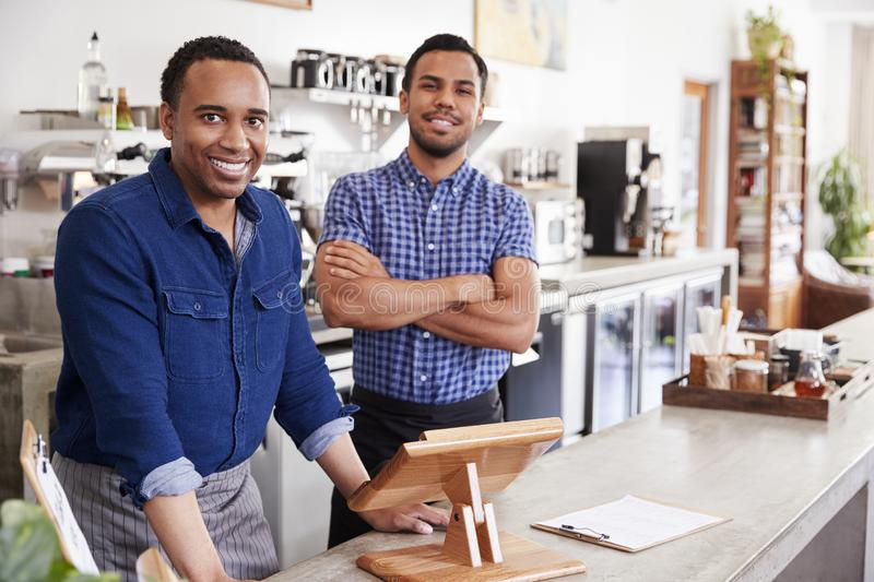Two male owners behind the counter at their coffee shop stock photo
