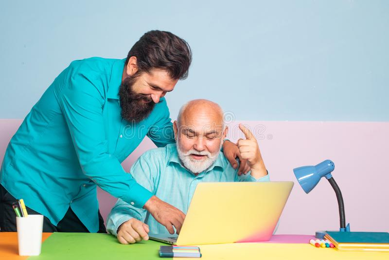 Two male senior man employees consulting with laptop in office. Conversation between colleagues in office. Business. Two male senior men employees consulting royalty free stock image