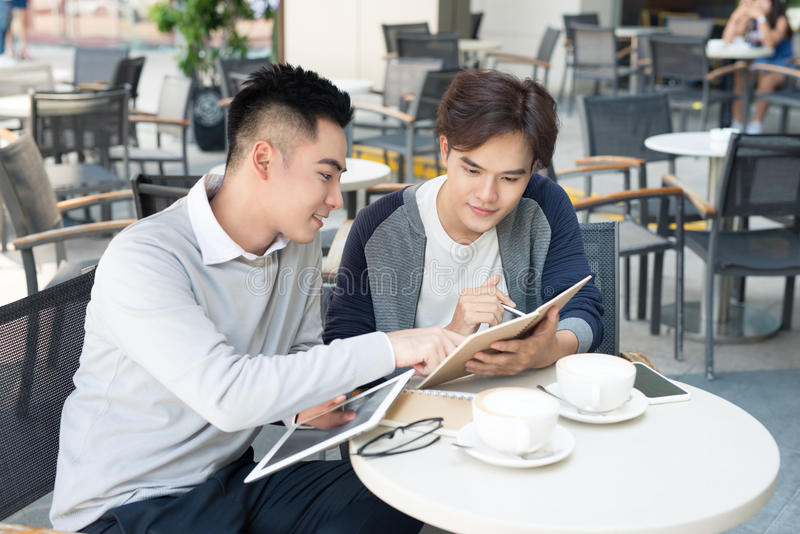 Two male student learning or entrepreneur working together. stock image
