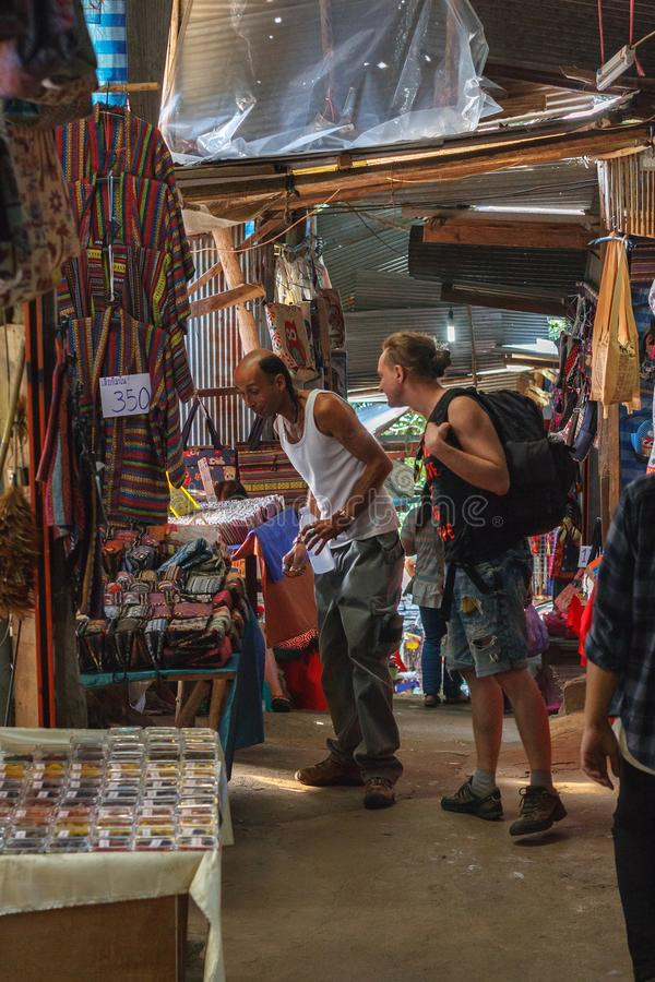 Two male tourists choosing souvenirs at Doi Pui hill tribe village, handicraft market of the ethnic minority of miao or. Doi Pui hill tribe village, handicraft royalty free stock photos