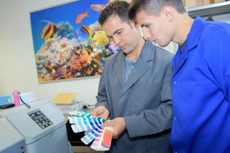 Two male workers looking at colour charts. Printing royalty free stock photo