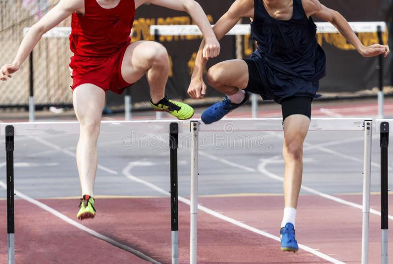 Two males running 400 meter hurdles. Two high school boys are even as they enter thr final straightaway during a 400 meter hurdle race stock images