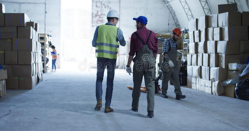 Two man discussing in a warehouse. Medium shot of two man discussing in a warehouse stock photo