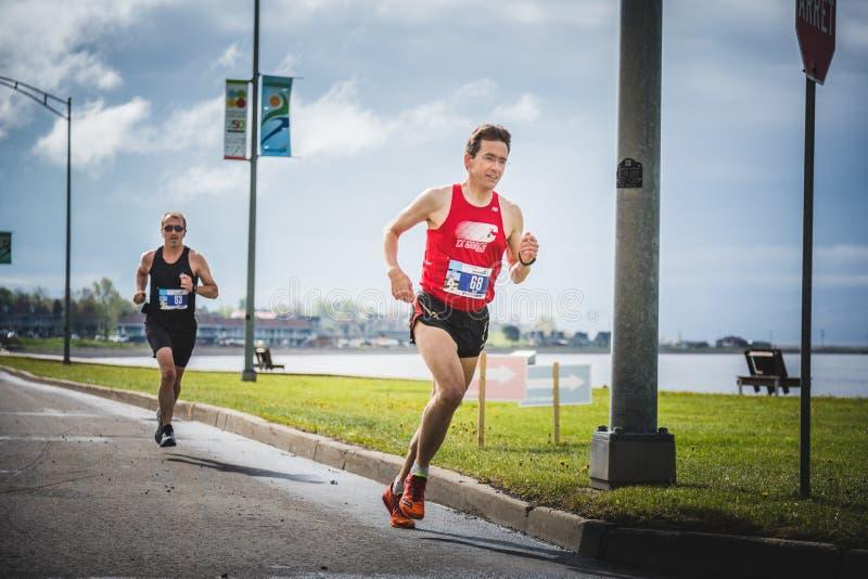 Two man doing the marathon. CARLETON, CANADA - June 4, 2017. During the 5th Marathon of Carleton in Quebec, Canada. Two man doing the marathon royalty free stock images