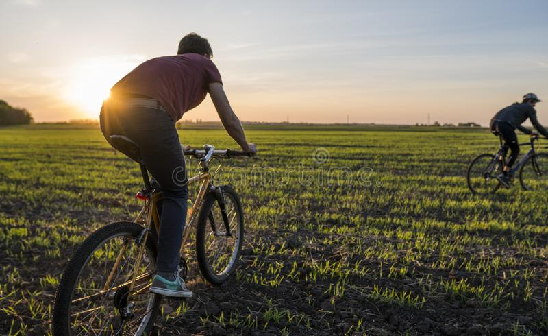 Two man ride a bicycle in sunset. Riding a Bicycle at Sunset. Healthy Lifestyle Concept. Male ride bicycle in sun set royalty free stock photos